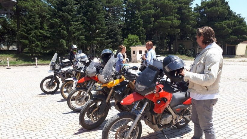 row of parked bikes and bikers on the silk road