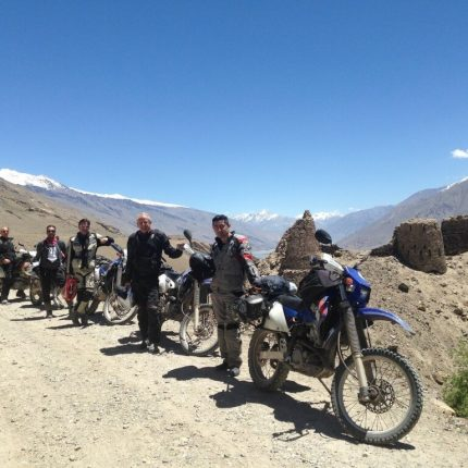 biker crew posing together in front of ruins with bikes
