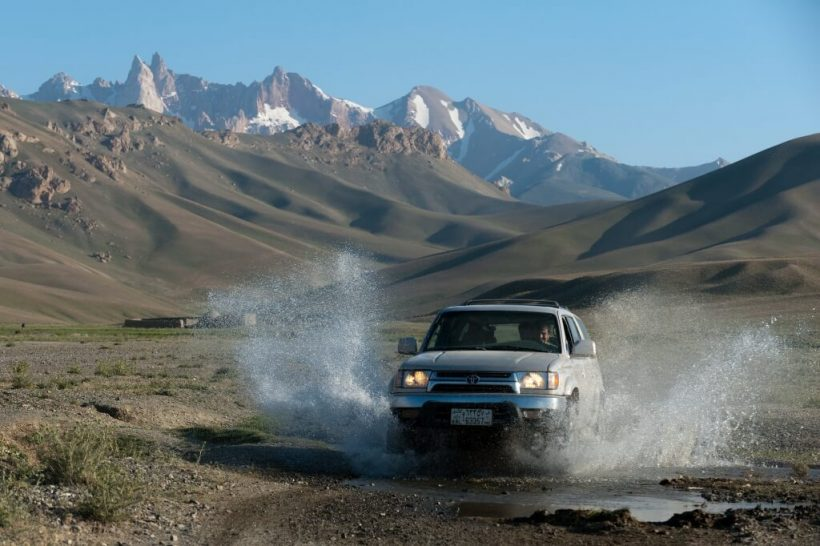 A jeep splashes through a stream in Bamiyan province