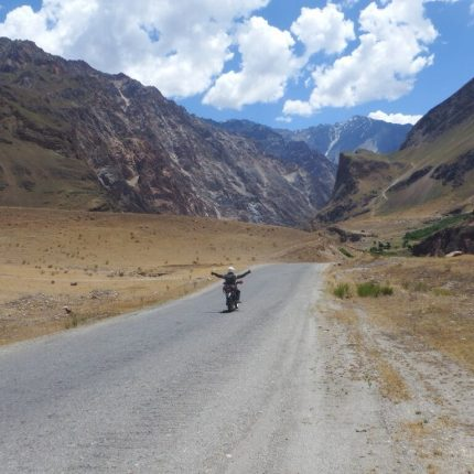 happy biker exploring the tajikistani mountains